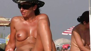 Nudist on the beach with big boobs is taking a shower